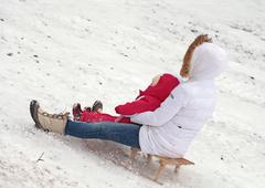 Mother and daughter sledding at winter Stock Photos