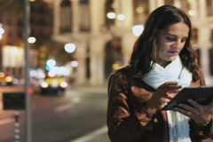 Woman surfing on tablet at night on the street, steadycam shot Stock Footage
