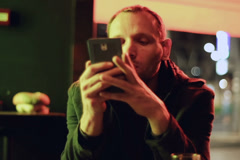 Irritated man checking cellphone at night in pub, steadycam shot Stock Footage