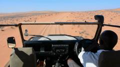 Namibia Northern Desert of Namib Desert riding safari vehicle in sand dunes of Stock Footage