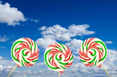 Three sugar lollipops in white green and red on background of sk - stock photo