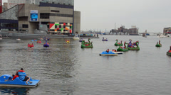 Baltimore Maryland Inner harbor with families out of dragon boats peddling for Stock Footage
