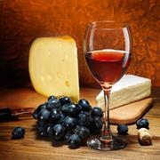 Cheese, grapes and glass of red wine. Stock Photos