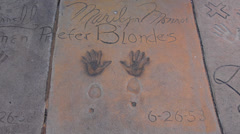 Los Angeles California CA Maryln Monroe hands and feet in cement at the famous Stock Footage