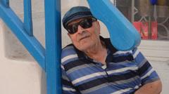 Mykonos Greece old Greek man with Greek hat under blue stairs 15 Stock Footage