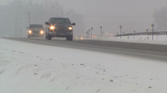 Traffic driving in snow storm around curve on snow covered road Stock Footage