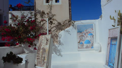 Greece Santorini Oia Cyclades art gallery with flowers white buildings and steep Stock Footage