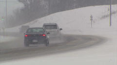 Cars driving in snow storm around curve on road Stock Footage