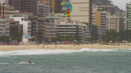 Stock Video Footage of Pan shot of parasailing surfer with Cityscaper in the background.