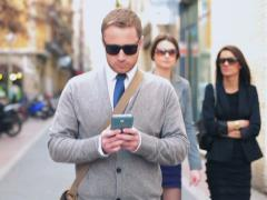 Man walking down the street and using cellphone, steadycam shot Stock Footage