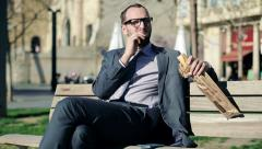 Young handsome businessman eating baguette in the city HD Stock Footage