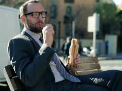 Young handsome businessman eating baguette by the city street NTSC Stock Footage