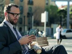 Businessman listening music on smartphone and eating baguette in the city NTSC Stock Footage