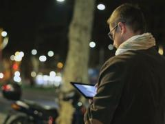 Man walking down the street at night and using tablet, steadycam shot Stock Footage