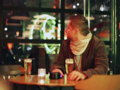 Anxious man waiting in pub and drinking beer, steadycam shot Stock Footage