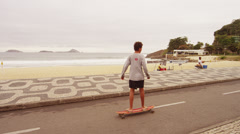 RIO DE JANEIRO, BRAZIL - JUNE  23: Slow dolly shot of skateboard boy at Ipanema Stock Footage