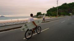 RIO DE JANEIRO, BRAZIL - JUNE  23: Dolly shot, biker + surfboard, Ipanema Beach Stock Footage