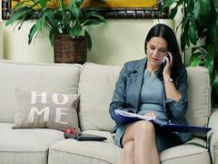 Businesswoman talking on cellphone and reading documents on sofa NTSC Stock Footage