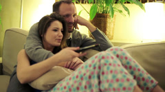 Young couple on sofa watching tv at home HD Stock Footage