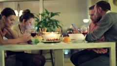 Friends with smartphone sitting by the dinner table at night HD Stock Footage