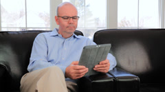 Mature Baby Boomer Bald Man Reading Tablet iPad Sat In A Chair At Home - stock footage