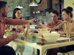 Friends looking at funny things on smartphone during dinner NTSC Stock Footage