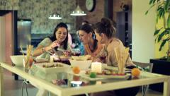 Three girlfriends with smartphone by the dinner table at party HD Stock Footage