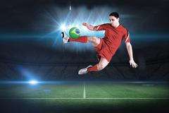 Stock Illustration of Composite image of fit football player jumping and kicking