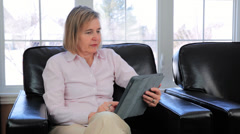 Mature Baby Boomer Woman Using An iPad Sat In A Chair - stock footage