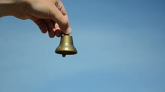 Male and female hands ding with silver bronze bell on blue sky Stock Footage