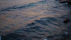 Following a wave break on a rocky beach Stock Footage