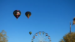 Black Hot Air Balloons Float Over a Ferris Wheel Stock Footage