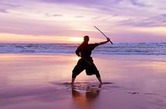 Young samurai women with japanese sword(katana) at sunset on the beach Stock Photos