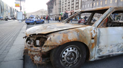 Burned shell of a car in foreground of ukrainian square used in protests Stock Footage