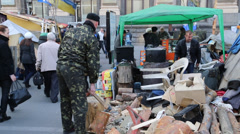 Soldier splits firewood wood as other protesters mingle near maidan square, Stock Footage