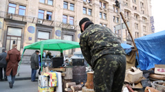 Soldier splits firewood wood as other protesters pass by near maidan square, Stock Footage