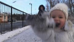 Happy Girl play snow on wayside, run and laugh to catch camera. Steady Cam. Stock Footage