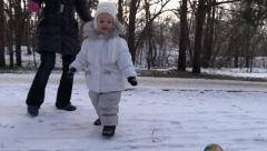 Girl absorbedly play football with mom on first snow in the park. Steady Cam Stock Footage