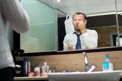 man applying an eye cream and standing before the mirror - stock footage