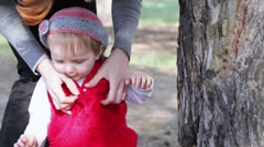 Dress child. Year-old baby mama dress on nature Stock Footage
