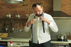 Young businessman tying his tie and eating breakfast in the kitchen Stock Footage