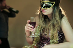 Drunk woman in a mask with a glass of wine  and a drunk man in the background Stock Footage