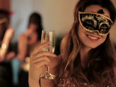 beautiful woman in a mask toasting and drinking wine to the camera - stock footage