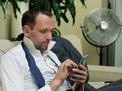 Businessman sitting on the sofa and using his cellphone Stock Footage