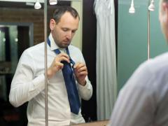 Young businessman tying his tie and looking in the mirror Stock Footage