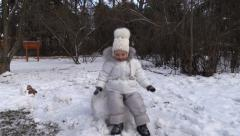 Little girl sits on the snow in winter park. Steady cam. Stock Footage
