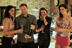 Man opening the bottle of champagne and pouring into women's glasses Stock Footage
