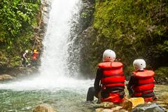 Couple Of Tourist Admiring The Natural Beauty Of A Waterfall Canyoning Trip Stock Photos