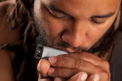 Rastafarian Man Playing Mouth Harmonica Stock Photos