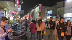 Man sits on scooter to use phone at taichung night market Stock Footage